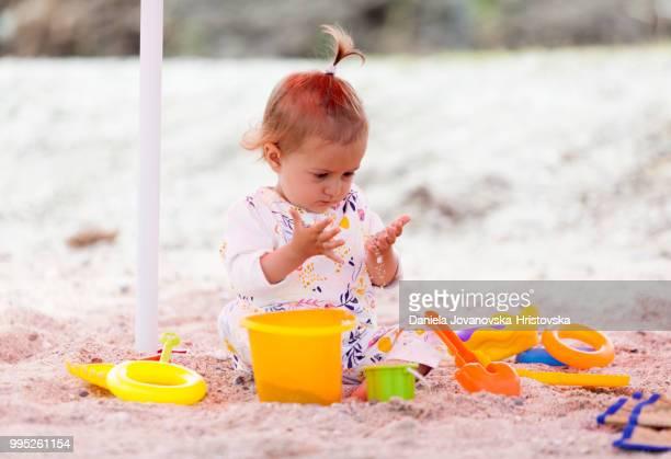petite fille jouant avec des jouets dans le sable