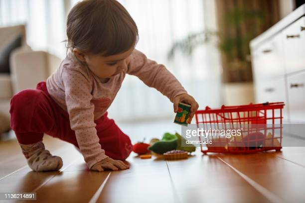 baby girl playing with toys - damircudic stock photos and pictures