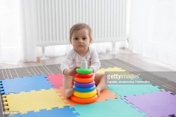 baby girl playing with toys - pyramid shapes around the house stock pictures, royalty-free photos & images