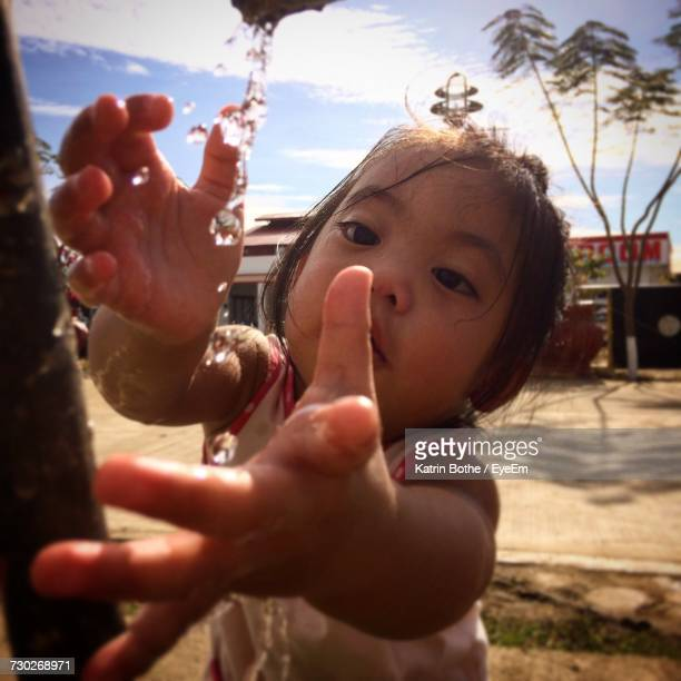 Baby Girl Playing With Water Against Street