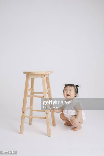 Baby girl playing with wooden high chair
