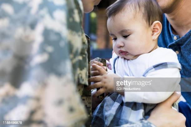 baby girl plays with her mom's dog tags - military dog tags stock pictures, royalty-free photos & images