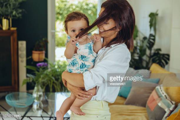 baby girl pulling mother?s hair in living room - pulling stock pictures, royalty-free photos & images