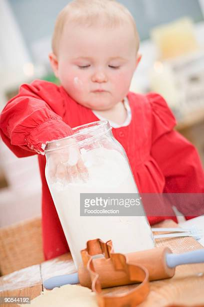 baby girl (0-11 months) reaching into jar of flour - 0 1 months stock pictures, royalty-free photos & images