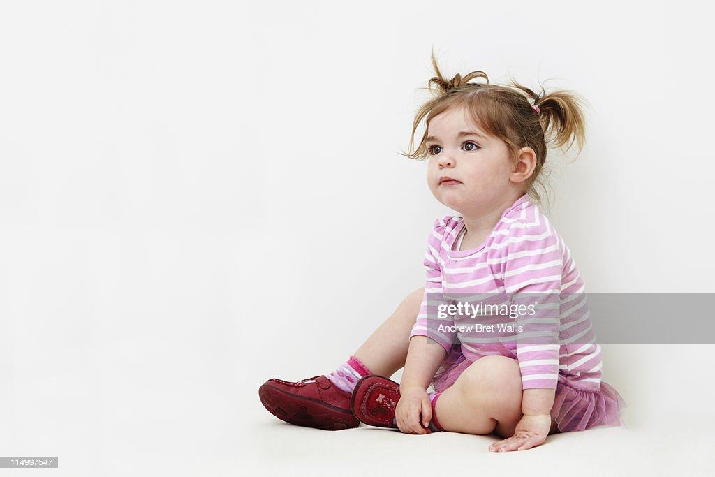 Baby girl seated on a white background : Stockfoto