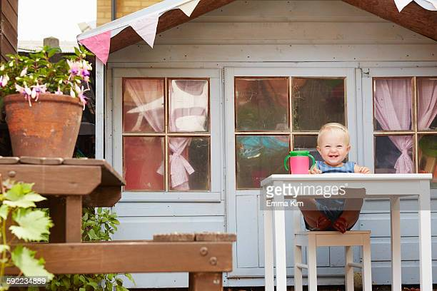 Baby girl sitting at table in front of playhouse looking at camera smiling