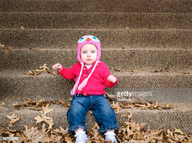 Baby girl sitting in autumn leaves on front steps