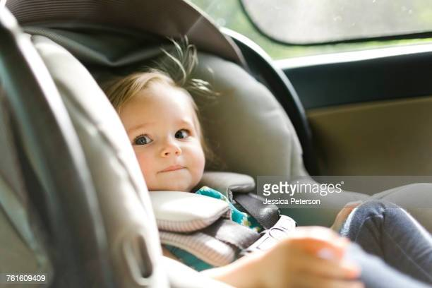 Baby girl (12-17 months) sitting in baby car seat during car trip