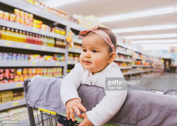 Baby girl sitting in grocery cart