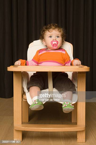 Baby girl (6-9 months) sitting in high chair, pacifier in mouth
