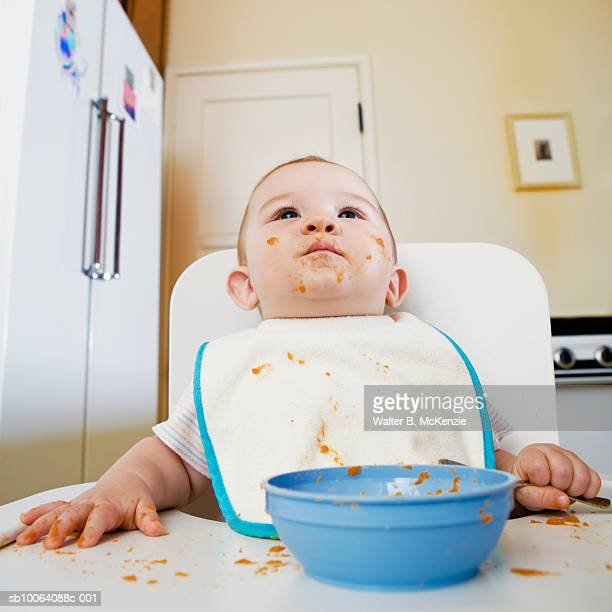 Baby girl (6-7 months) sitting in high chair with bowl of baby food in front