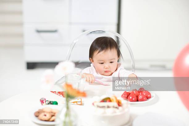 Baby girl (15-18 months) sitting in highchair at table