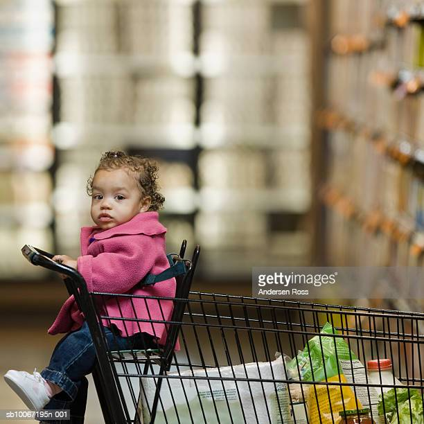 Baby girl (12-15 months) sitting in shopping trolley, portrait