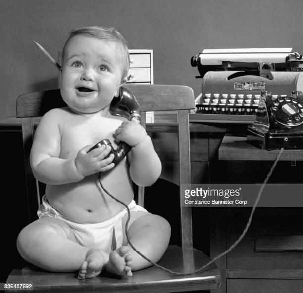 baby girl sitting office chair hold retro telephone - constance bannister stock photos and pictures