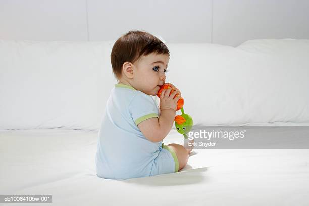 Baby girl (15-18 months) sitting on bed, biting toy