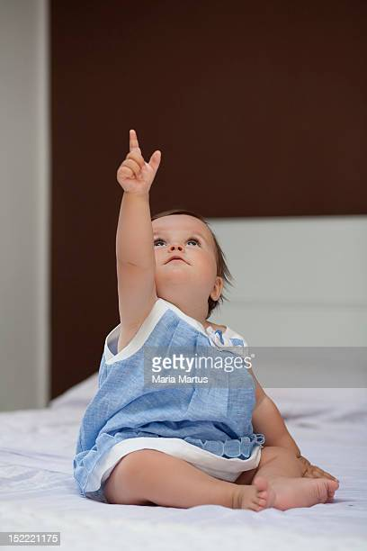 baby girl sitting on bed - baby pointing stock photos and pictures
