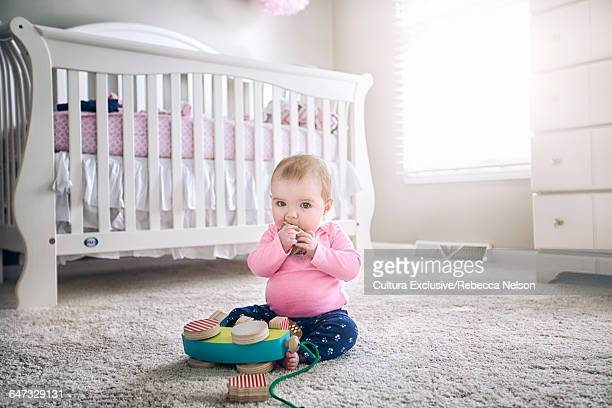 Baby girl sitting on carpet with wooden toy, hands to mouth looking at camera