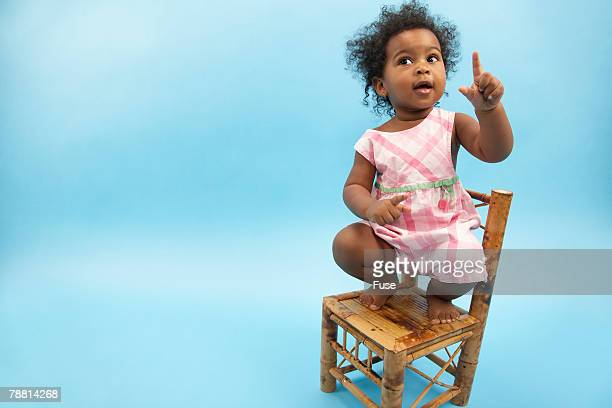 baby girl sitting on chair - baby pointing stock photos and pictures