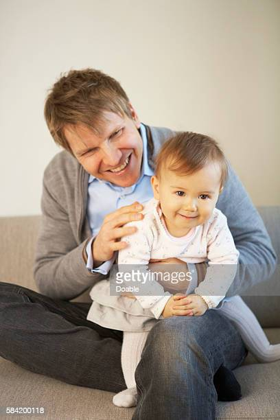 baby girl sitting on father's lap - genderblend stock pictures, royalty-free photos & images