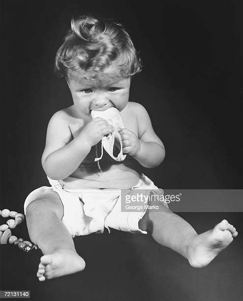 Baby girl (9-12 months) sitting on floor, holding shoe in mouth (B&W)