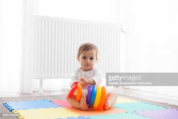 baby girl sitting on floor playing with toys - pyramid shapes around the house stock pictures, royalty-free photos & images