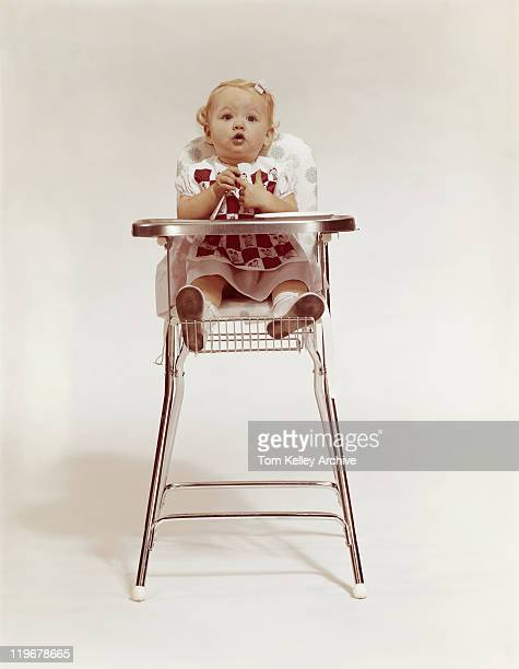 Baby girl sitting on high chair