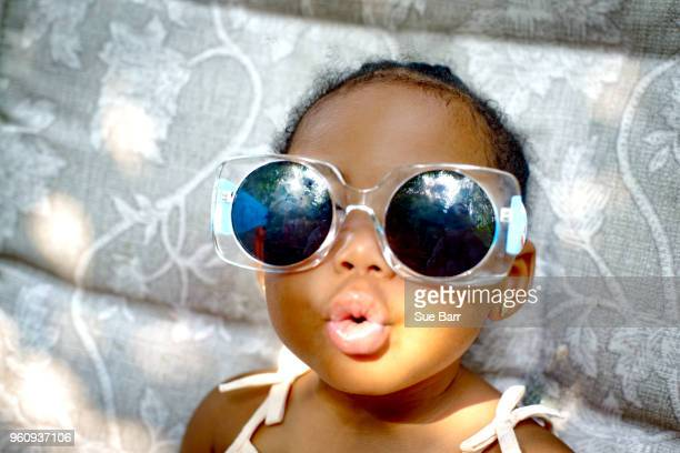 baby girl sitting on lounge chair wearing sunglasses, portrait - funny black girl stock photos and pictures