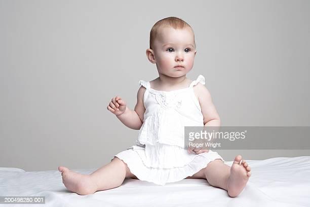 Baby girl  (6-9 months) sitting, portrait