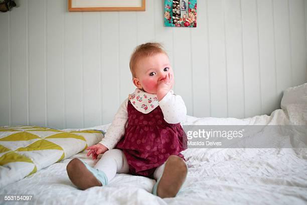 Baby girl sitting, sucking her thumb