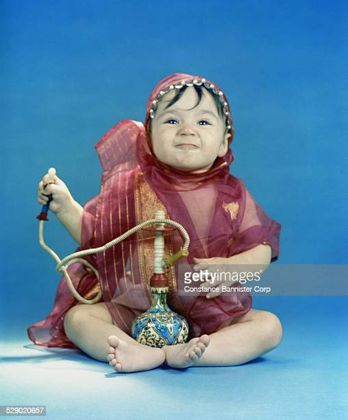 Baby girl sitting wrapped in silk scarf holding a bottle pipe