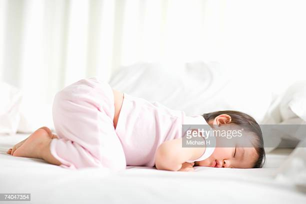 Baby girl (15-18 months) sleeping on bed