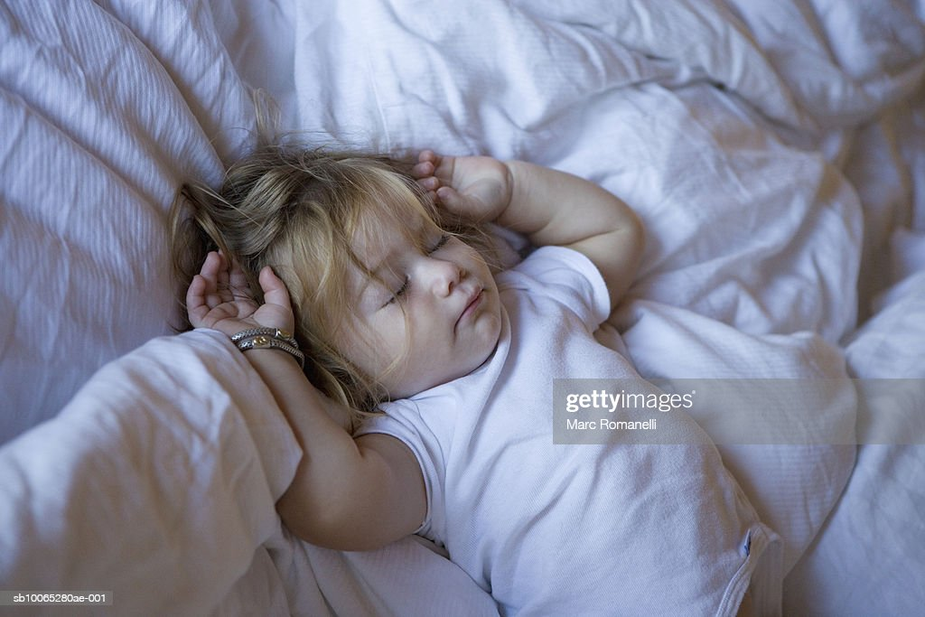 Baby girl (9-12 months) sleeping on bed : Foto stock