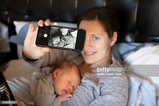Baby girl sleeping on mothers chest, while mother takes self portrait of them both, using smartphone