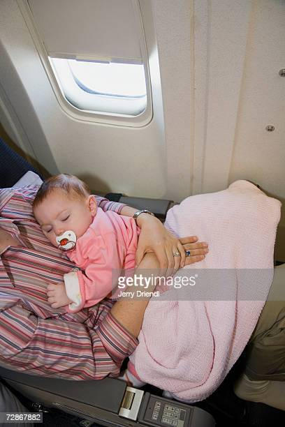 Baby girl (6-9 months) sleeping on mother's lap on airplane, elevated view