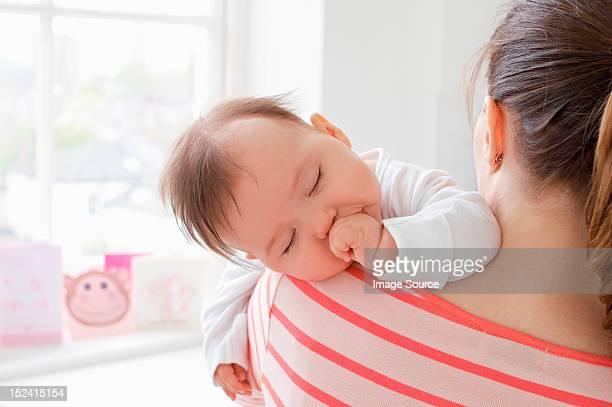 Baby girl sleeping on mother's shoulder