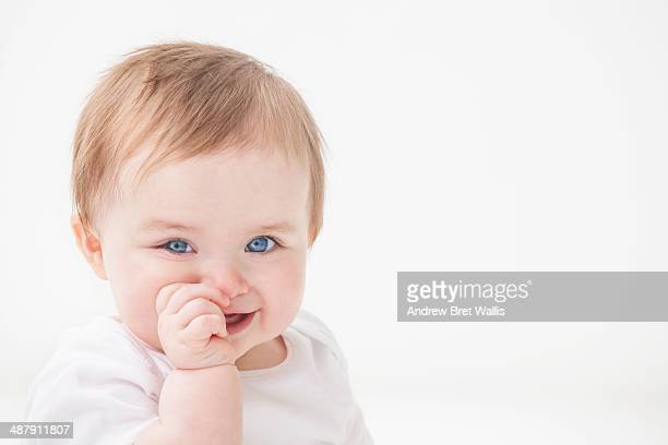 Baby girl smiling and sucking her thumb