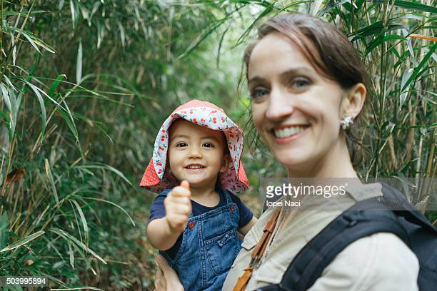 Baby girl smiling at camera with mother in nature
