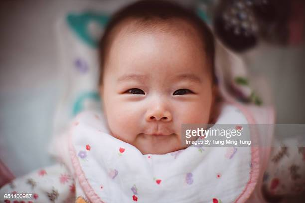Baby girl smiling joyfully at camera