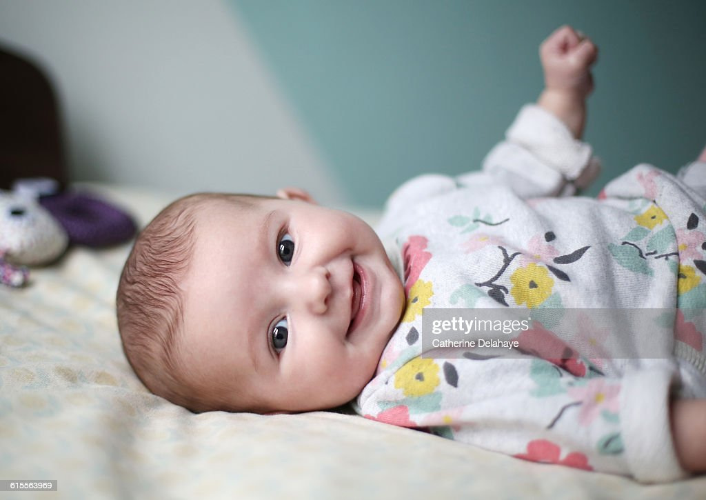 A baby girl smiling on a bed : Stockfoto