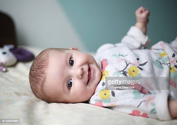 a baby girl smiling on a bed - baby girls stock pictures, royalty-free photos & images