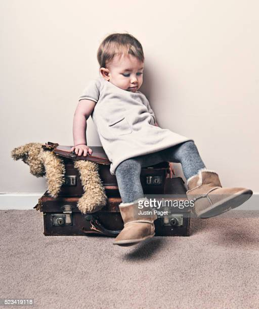 Baby Girl Squashing Teddy into Suitcase