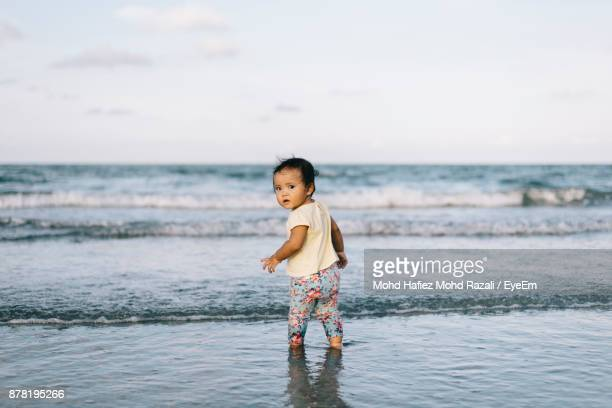 baby girl standing at beach against sky - malaysia beautiful girl stock photos and pictures
