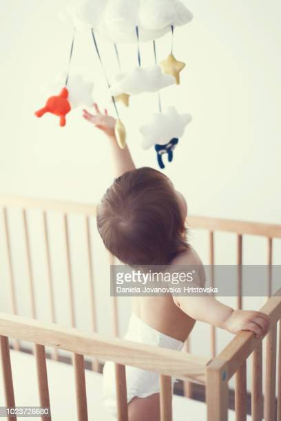 baby girl standing in baby crib playing