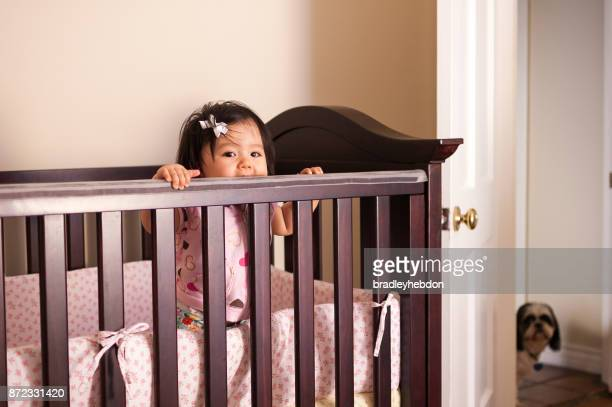 Baby girl standing in her wooden crib