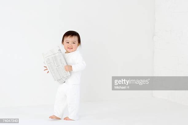 Baby girl (15-18 months) standing in studio, holding newspaper