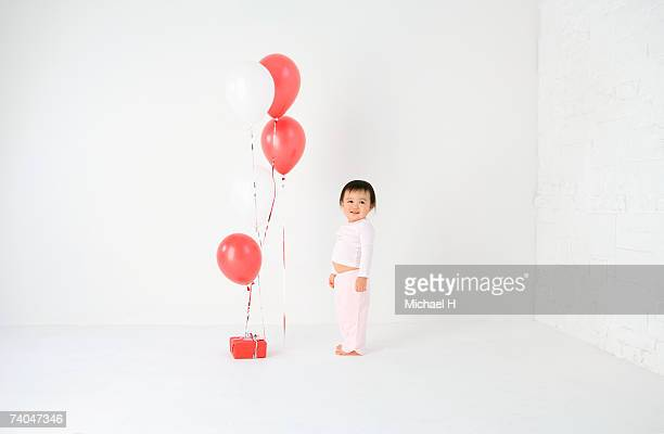 Baby girl (15-18 months) standing in studio with balloons and present
