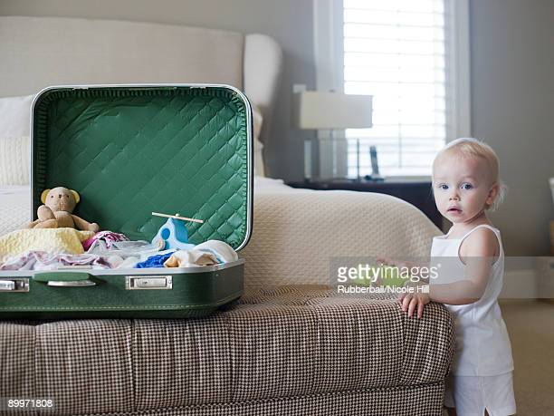 baby girl standing next to open suitcase