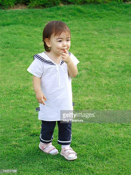 baby girl standing on a lawn - 1歳以上2歳未満 ストックフォトと画像