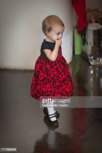 baby girl standing on floor at home - marty hardin stock photos and pictures