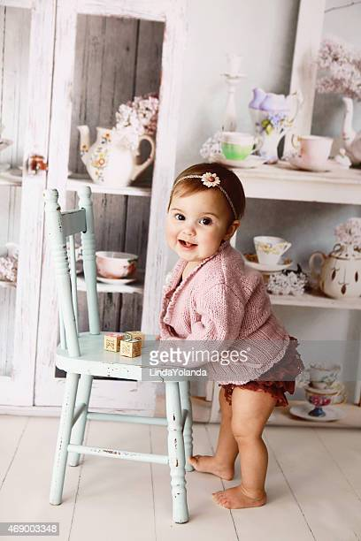 Baby girl standing while holding a blue wooden chair